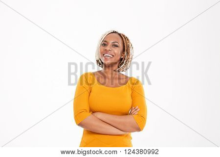 Cheerful cute lovely young african american woman standing with hands folded over white background