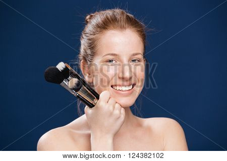 Smiling woman holding makeup brushes over blue background