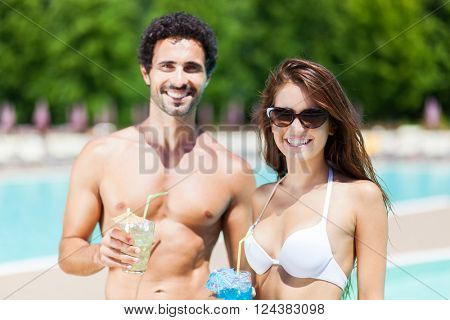 Couple enjoying a cocktail by the pool side