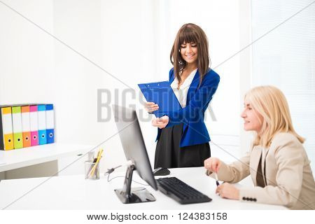Smiling woman working together in their office. Focus on the woman in background
