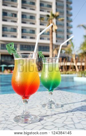 Two glasses with colored cocktails are around the pool