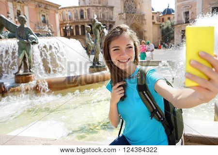 Woman tourist taking selfie pictures on Europe travel. Happy candid tourist on Valencia Spain. Travel and tourism concept.