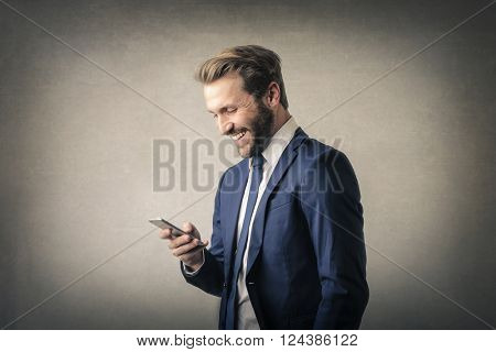 Laughing businessman with smartphone