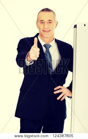 Male executive with ok sign near flip chart