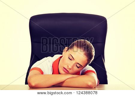 Tired young female doctoror nurse sleeping on the desk