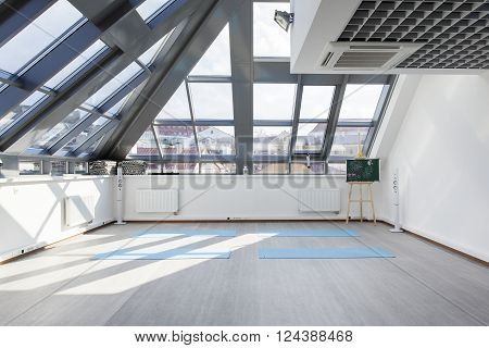 A place for sports training in yoga and fitness. Several mats lie on the floor. The interior gym with a large window in the ceiling and patches of sunlight on the white wall.