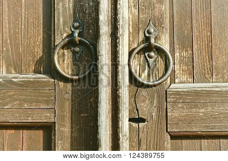 Aged brass door handles in the form of ring at the timbered ancient weather-beaten door. Architectural background. Vintage tones processing