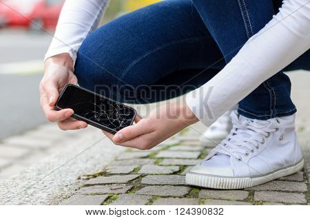 Young Woman Picking Up Her Smashed Mobile
