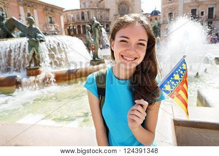 Happy tourist holding flag of Valencian Community. Young girl student exchange for learning the language. Valencia Spain. Travel and tourism concept.