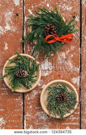 Three Christmas advent wreaths on wooden table