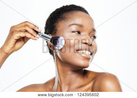 Smiling afro american woman applying makeup with brush isolated on a white background
