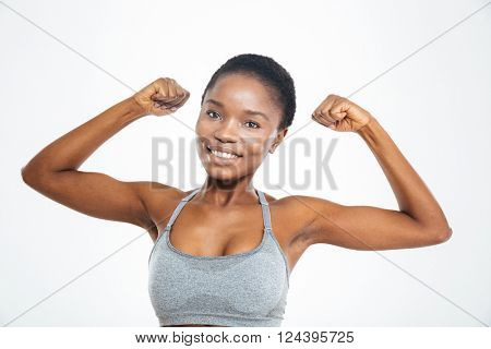 Smiling afro american woman showing her biceps isolated on a white background