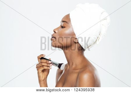 Side view portrait of afro american woman applying makeup with brush isolated on a white background