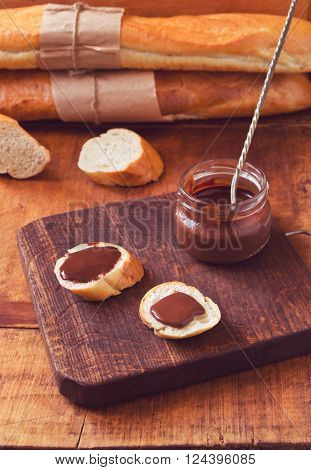 Snack with French baguette and chocolate ganache on dark wooden table