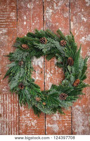 Handmade Christmas advent wreath with fir cones on wooden table
