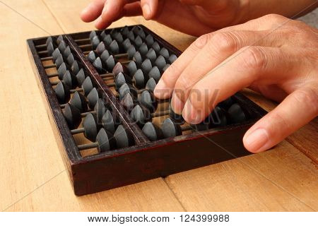 Human hand uses abacus on the table