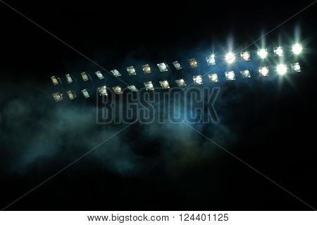 Stadium lights and smoke against dark night sky