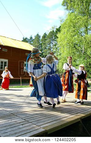 HELSINKI FINLAND - JUNE 20 2012: Unidentified dancers in folklore ensemble in traditional folk costumes at midsummer day festival.
