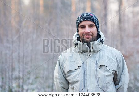 Portrait of a handsome man with rugged stubble, wearing warm clothes while standing outdoors on a cold winter day, looking at the camera with a subtle smile and a snowy forest behind him