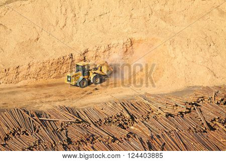 Yellow excavator works with lots of sawdust