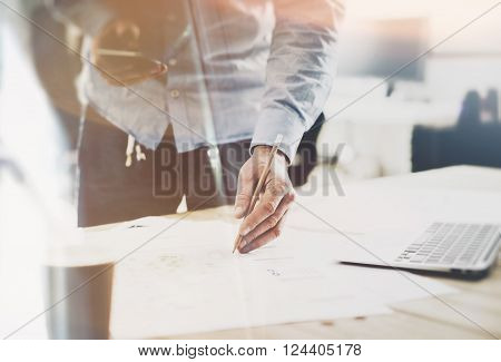 Working process startup. Architect working at the wood table with new building project. Modern notebook on table. Pencil holding hand. Horizontal mockup. Flares, film effect.