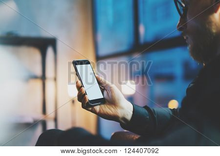 Closeup photo businessman relaxing on modern loft office. Man sitting in chair at night. Using contemporary smartphone, blurred background. Blank screen ready for your business information.