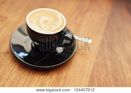 One modern black ceramic cup and saucer on a wooden counter, with a freshly made cappucino that has a swirling pattern created in the frothed milk