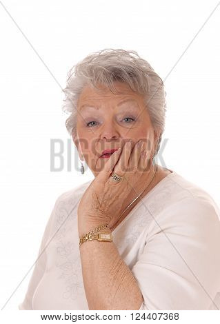 A lovely senior woman in her seventies holding her face in her hand and