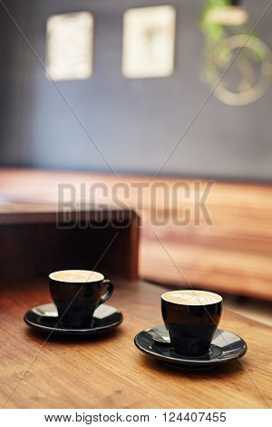 Wooden counter in a coffee shop with two cappucinos in modern black ceramic cups with saucers