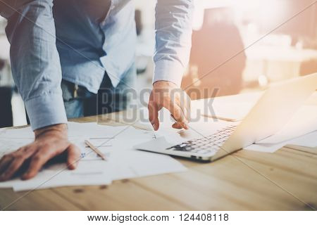 Office world. Businessman working at the wood table with new business project in modern coworking place. Man touching pad contemporary laptop. Horizontal mockup.