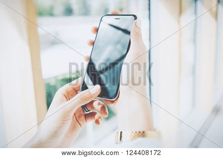 Photo young woman looking smartphone in hands. Open space loft office. Panoramic windows background. Horizontal mockup.