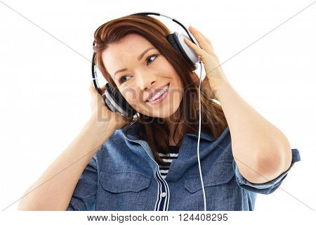 Young woman listen to music on her headphones, isolated over white background