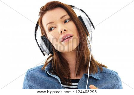 Young woman listen to music on her white headphones, isolated over white background
