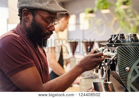 Hansome African man with a beard and hipster style, using a modern espresso machine to froth milk in a coffee shop