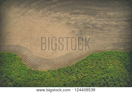 Photo from above of raked sand and grass