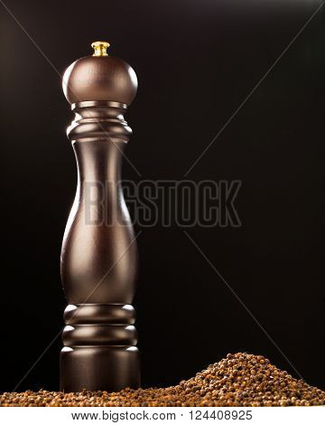 pepper mill and peppercorns heap, black background
