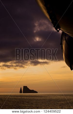 Sunset with a small island on the horizon. Life boats in the foreground. Near San Cristobal Island Ecuador.