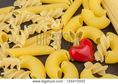 We love pasta. Different kinds of pasta on the kitchen table. Preparation of pasta. Healthy food.