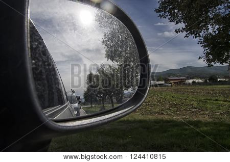 View of the Tuscan landscape in the rearview mirror