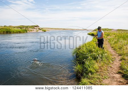 Middle aged man fishes caught salmon from the river. Far East Russia.