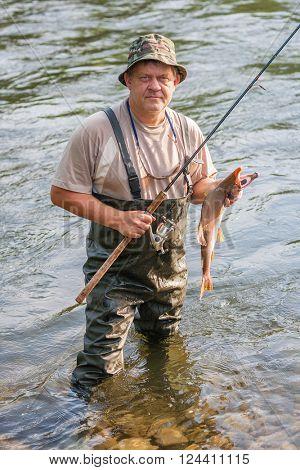 Fisherman keeps caught salmon (pink salmon). Far East Russia.