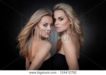 Two sexy girls in casual clothes posing on dark background