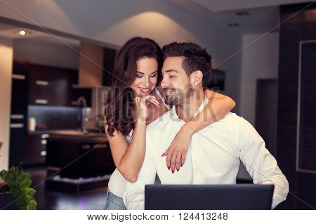 Happy young caucasian couple at home woman embrace man at laptop