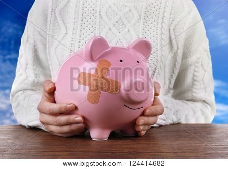 Woman holding Piggy Bank with adhesive bandage, on blue sky background