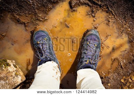 Top view of hiking boots in the mud.