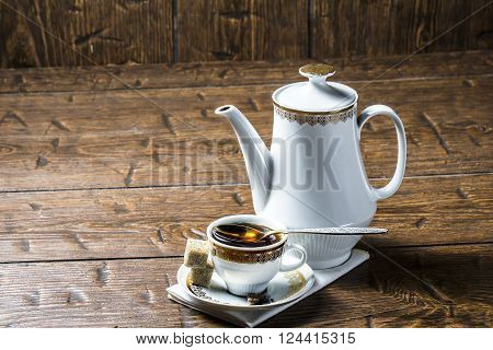 Coffee pot and coffee Cup with silver spoon on a wooden table