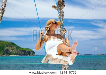 Woman in white dress and hat swinging at tropical beach, sunny day, good weather