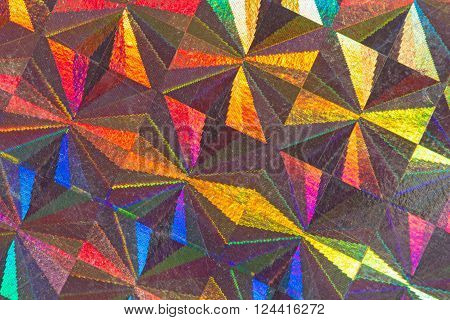 Multicolored psychedelic abstract formed by light reflecting off a textured metal surface