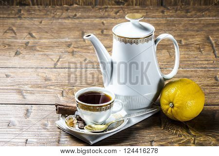Coffee pot with coffee Cup and lemon on a wooden table