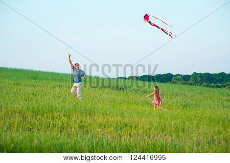Father with child to fly a kite at sunset.
